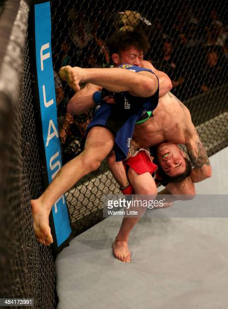 Tatsuya Kawajiri of Japan picks up Clay Guida during their bout during UFC Fight Night 39 at du Arena on April 11, 2014 in Abu Dhabi, United Arab...
