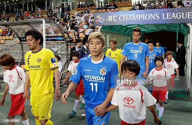 Tatsuya Masushima of Kashiwa Reysol and Lee Keun-Ho of Ulsan Hyundai lead the two sides to the field for the AFC Asian Champions League match between...
