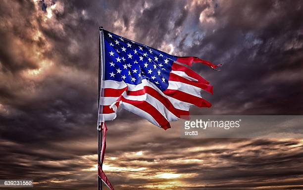 Tattered American flag flapping in ominous sky