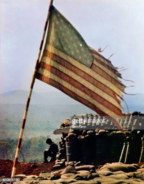 Tattered American flag flies above firebase LZ Lonely, and is typical of fortified positions used to support ground forces with artillery. A bullet...