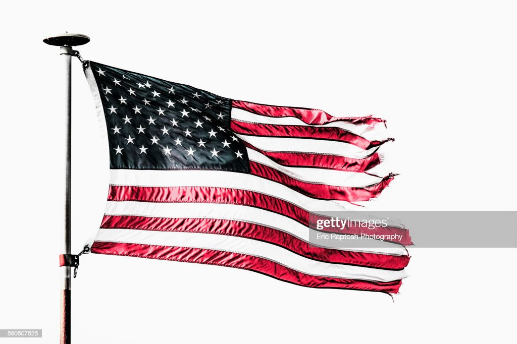 Tattered American flag flying from flagpole : Stock Photo