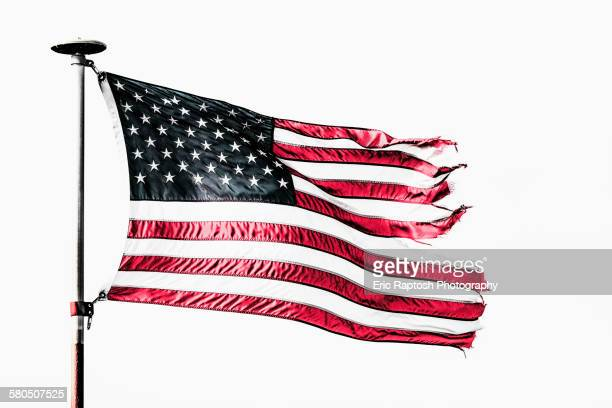 Tattered American flag flying from flagpole