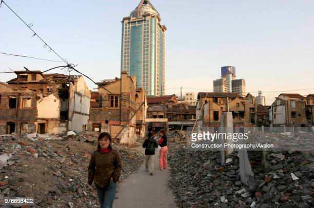 A tattered district in Shanghai with a skyscraper in the background