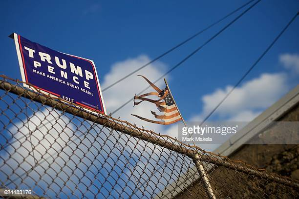 Tattered flag waves beside a Donald Trump campaign sign in the background of a residence on October 19, 2016 in Philadelphia, Pennsylvania.