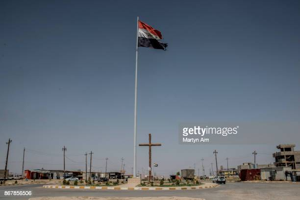 A tattered Iraqi flag flies above a cross in the Christian town of Qaraqosh in northern Iraq on September 8 2017