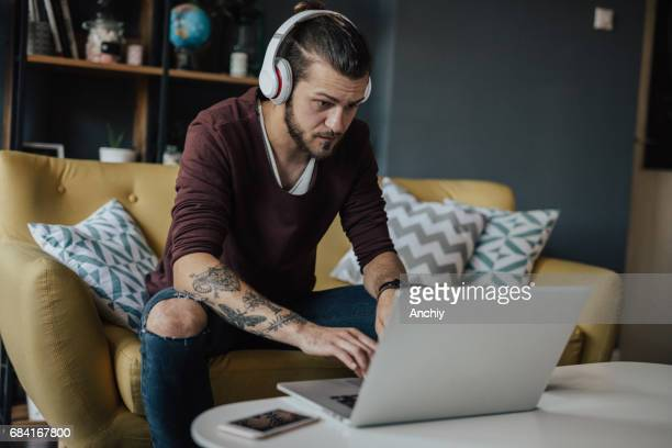Tattoed guy is listening to a podcast on his laptop