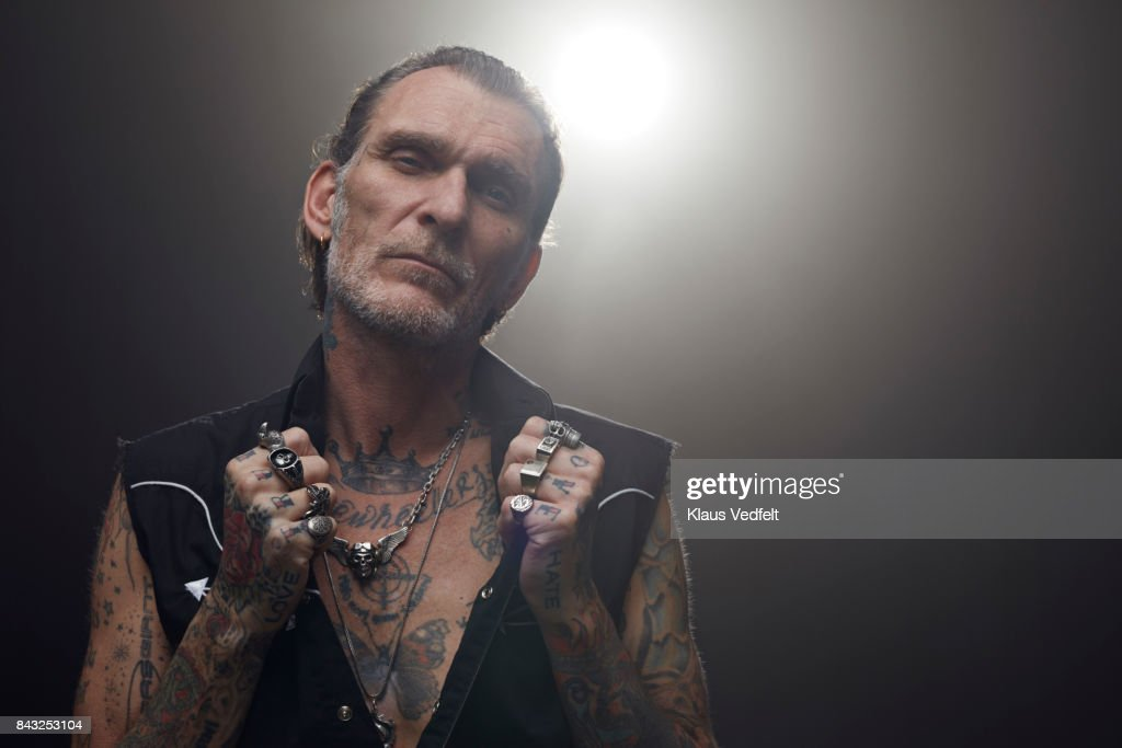 Tattoed mid aged man wearing lots of finger rings and looking in camera : Stock Photo