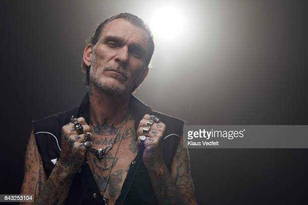 Tattoed mid aged man wearing lots of finger rings and looking in camera