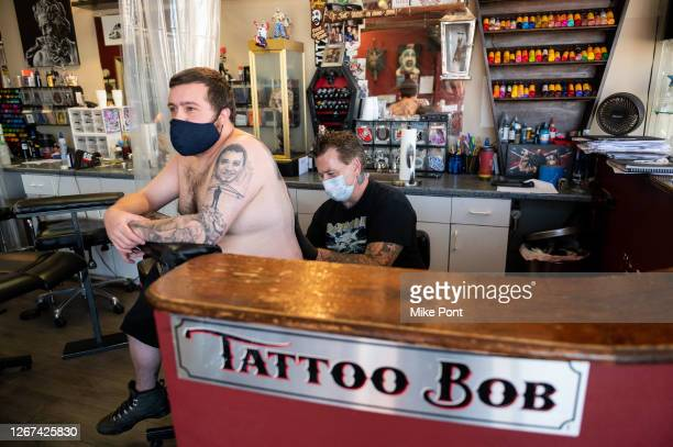 Tattoo artist and owner Bobby Petraglia wearing protective face mask tattoos a client at Skin Deep Tattoo as the city continues Phase 4 of re-opening...