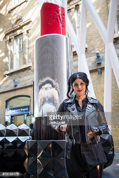 Tattoo artist and television personality Kat Von D poses by a giant lipstick at Kings Cross Station to mark the launch of the new Kat Von D Beauty...