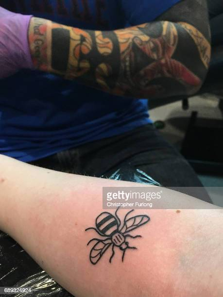 Tattoo artist Ben Rogers of Inkism Altrincham tattoos a worker bee the symbol of Manchester on the arm of Jess Mcgrath in memory of those who died in...