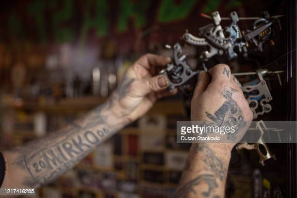 tattoo artist cleaning his tattoo machine stock photo - dusan stankovic stock pictures, royalty-free photos & images