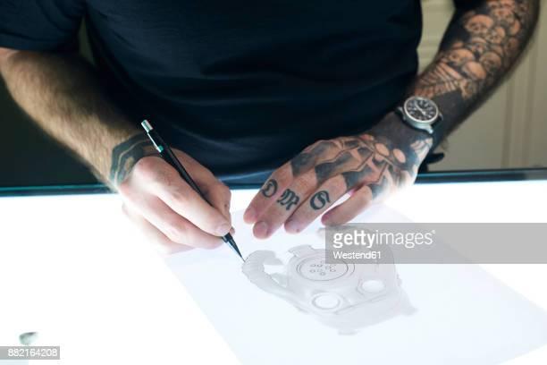 Tattoo artist designing motif on light table in studio