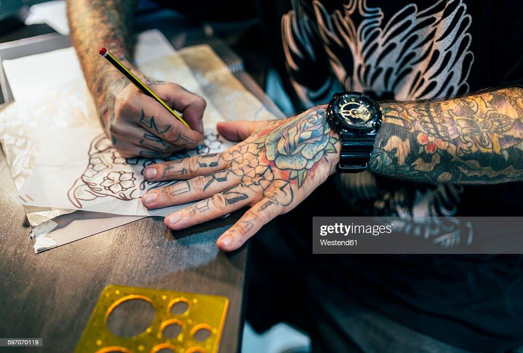Tattoo artist designing motifs : Stock Photo