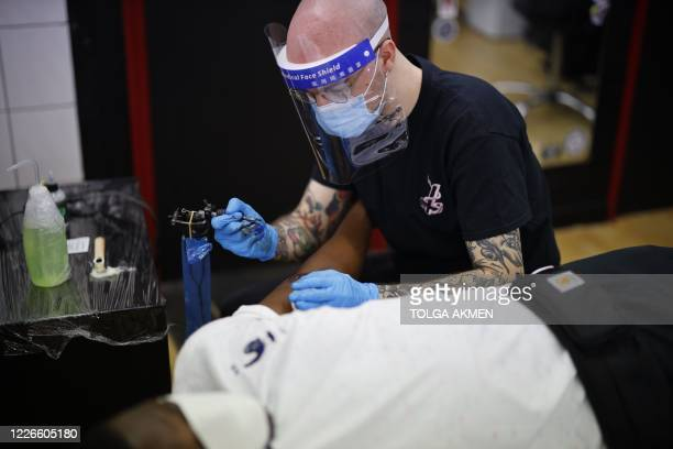 Tattoo artist Eloy Perez wearing a PPE visor and mask works on a customer at the Camden piercing and tattoo studio in north London on July 13 2020 as...