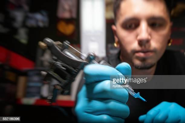 Artiste tatoueur tenant un pistolet avec aiguille jointe