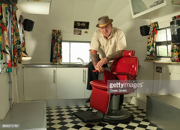 Tattoo artist in mobile tattoo parlour wearing pork pie hat looking at camera