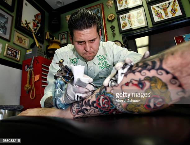 Tattoo artist Johnny Anderson owner of Yer Cheat n Heart Tattoo in Los Angeles works on a tattoo on Josh Such Anderson has sued the City of Hermosa...