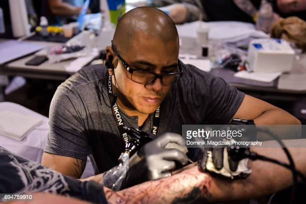 "Tattoo artist Jose Perez Jr. Tattoos a man during day two of the ""19th Annual Northern Ink Xposure Tattoo Convention"" at the Metro Toronto Convention..."