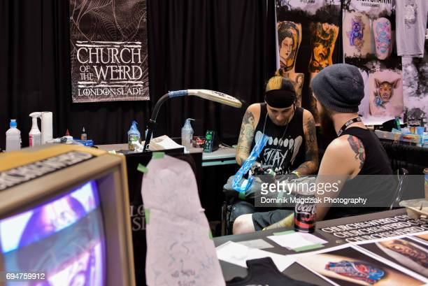 "Tattoo artist London Slade tattoos a man during day two of the ""19th Annual Northern Ink Xposure Tattoo Convention"" at the Metro Toronto Convention..."