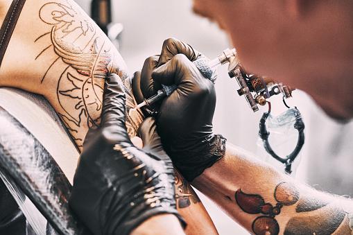 Tattoo Artist making a tattoo on a shoulder 1184219605