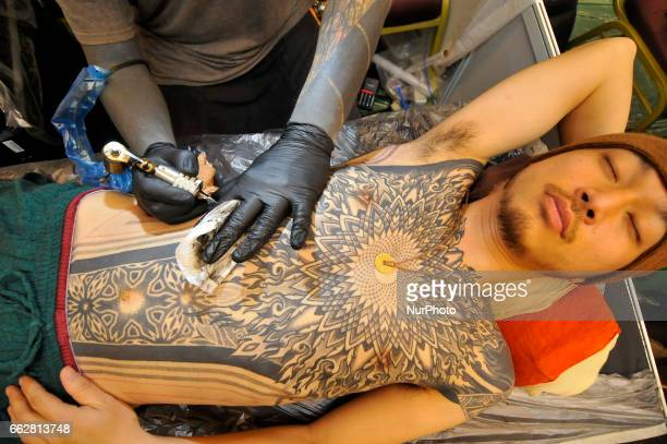 A tattoo artist making tattoo on a man during the 7th International Nepal Tattoo Convention in Lalitpur Nepal on Friday March 31 2017