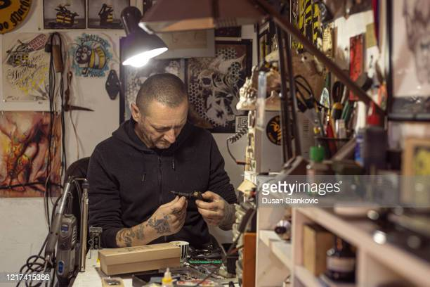 tattoo artist preparing his machine in the studio - dusan stankovic stock pictures, royalty-free photos & images