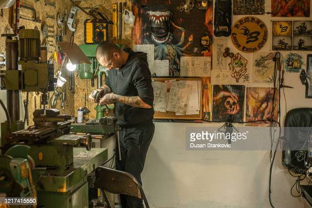 tattoo artist repairing tattoo machine in his workshop - dusan stankovic stock pictures, royalty-free photos & images