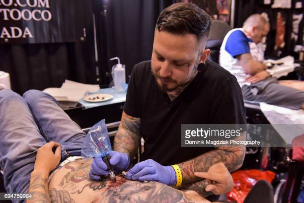 "Tattoo artist Ricke G tattoos a man during day two of the ""19th Annual Northern Ink Xposure Tattoo Convention"" at the Metro Toronto Convention Centre..."