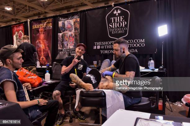 """Tattoo artist Ricke G tattoos a man during day two of the """"19th Annual Northern Ink Xposure Tattoo Convention"""" at the Metro Toronto Convention Centre..."""
