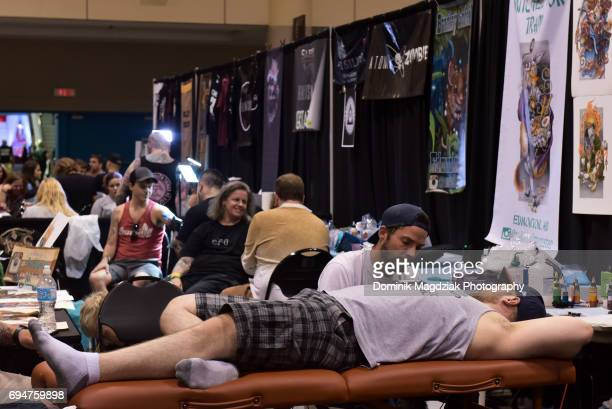"Tattoo artist tattoos a man during day two of the ""19th Annual Northern Ink Xposure Tattoo Convention"" at the Metro Toronto Convention Centre on June..."
