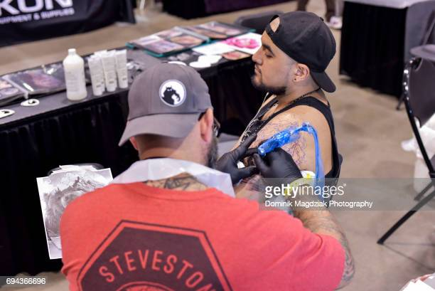 """Tattoo artist tattoos a mans arm during day one of the """"19th Annual Northern Ink Xposure Tattoo Convention"""" at the Metro Toronto Convention Centre on..."""