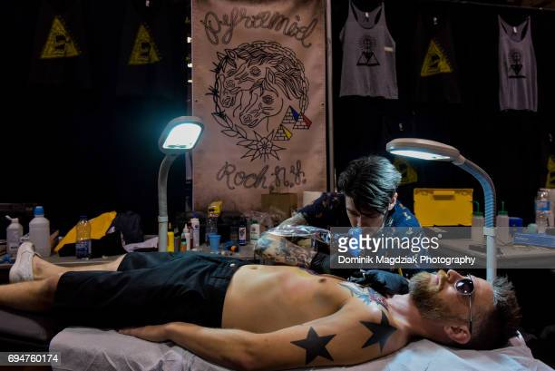 """Tattoo artist tattoos a mans chest during day two of the """"19th Annual Northern Ink Xposure Tattoo Convention"""" at the Metro Toronto Convention Centre..."""