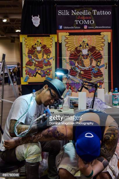 "Tattoo artist tattoos a mans shoulder during day two of the ""19th Annual Northern Ink Xposure Tattoo Convention"" at the Metro Toronto Convention..."