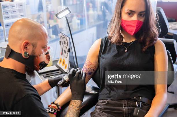 Tattoo artist wearing protective face mask tattoos a client at Skin Deep Tattoo as the city continues Phase 4 of re-opening following restrictions...