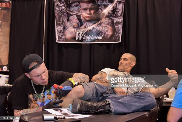 """Tattoo artist Whytebread tattoos a man during day two of the """"19th Annual Northern Ink Xposure Tattoo Convention"""" at the Metro Toronto Convention..."""