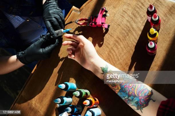 tattoo-experte in handschuhehalten tattoo pistole, während hand der weiblichen klientin mit neuen bunten tattoo liegen in holztisch neben, hoher winkel nahansicht - tätowierung stock-fotos und bilder