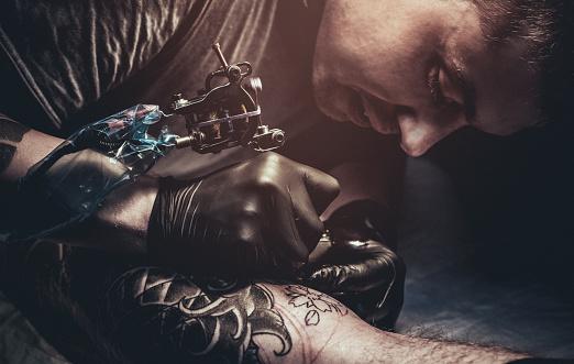Tattoo master making tattoo on customer's leg 872843542