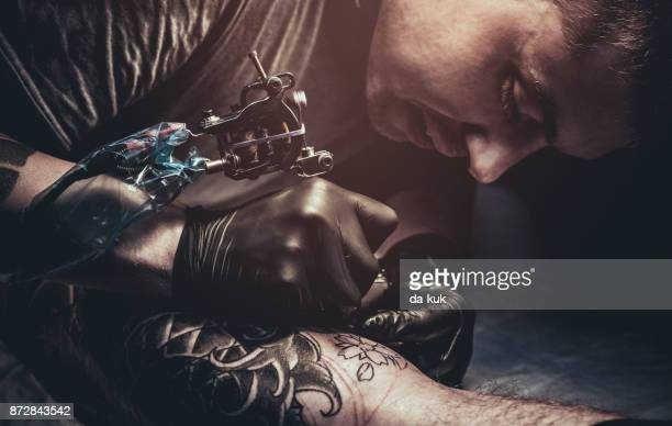 tattoo master making tattoo on customer's leg - tattoo stock pictures, royalty-free photos & images
