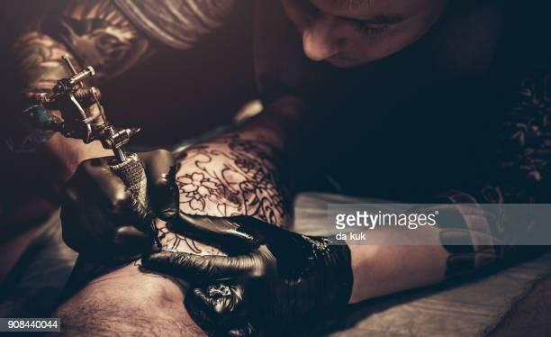 Maître de tatouage faire tatouage sur la jambe du client