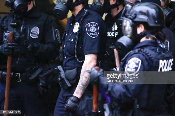 A tattoo of Abraham Lincoln is pictured on a Seattle Police officer arm as they stand by after protests against the death of George Floyd a black man...
