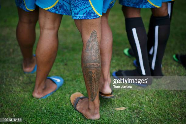 A tattoo on the calf of striker Alopua Petoa of the Tuvalu national football team as they train in a small park on a day off from matches in the...