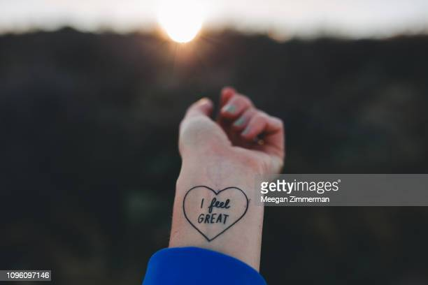 "tattoo stating ""i feel great"" on write - wrist stock pictures, royalty-free photos & images"