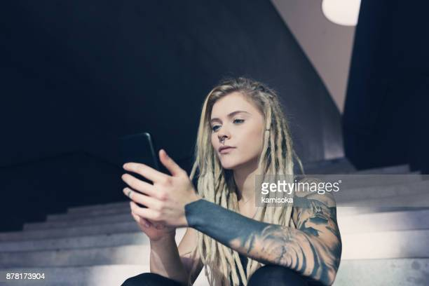 Tattooed and pierced young woman checking her smartphone