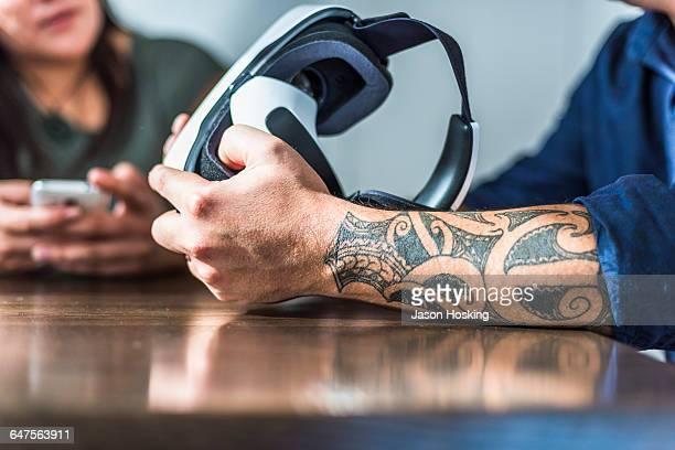 Tattooed arm of Polynesian man holding VR headset
