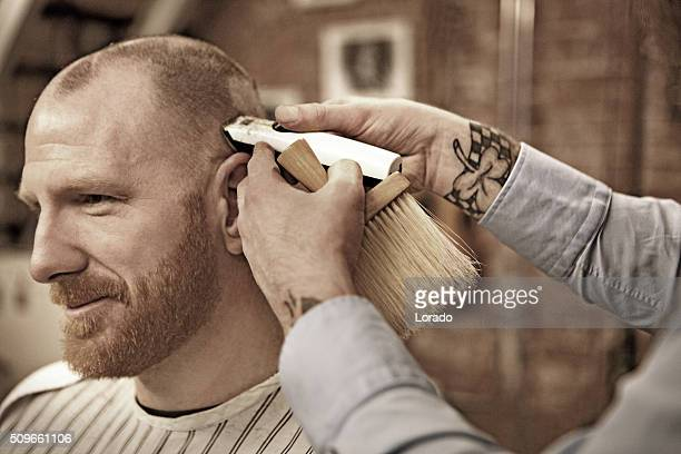 Tattooed barber with a bearded bald male client