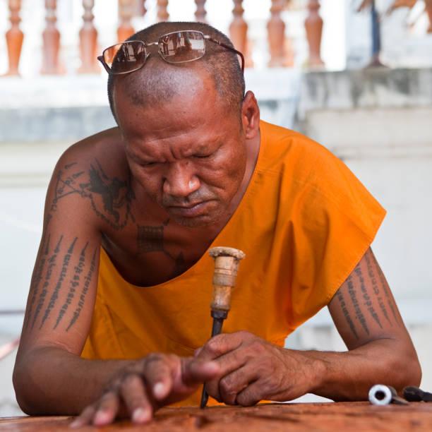 Tattooed Buddhist Monk outside Wat Sawang Fa Pruettaram, Pattaya, Thailand