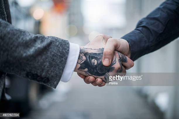 Tattooed businessman greeting colleague outdoors