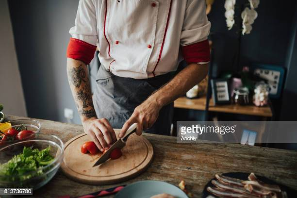 Tattooed chef cuts tomato into round slices