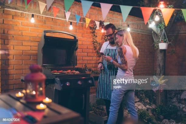 Tätowierte Paare, die Spaß am Grillen im Hinterhof